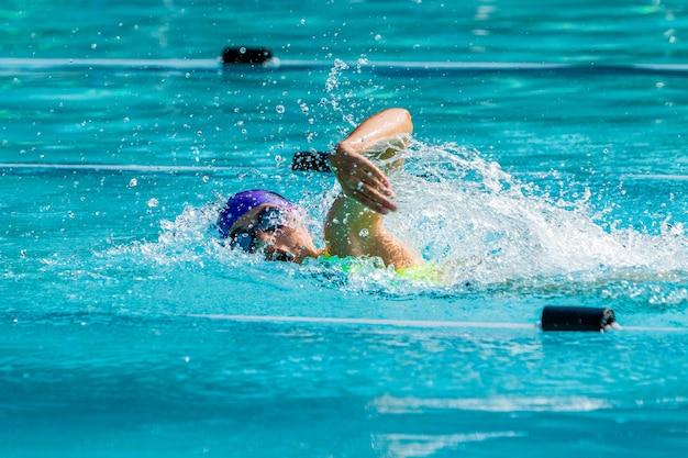 Młoda pływaczka pływa stylem dowolnym