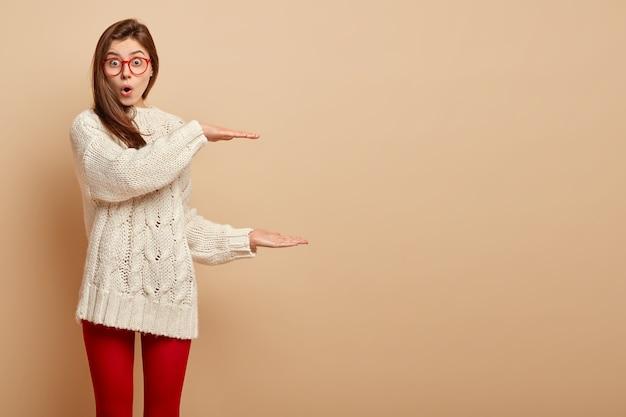 Młoda, pod wrażeniem, młoda kobieta ze zszokowanym wyrazem twarzy, kształtuje duży przedmiot, zdumiona rozmiarem, otwiera usta ze zdumienia