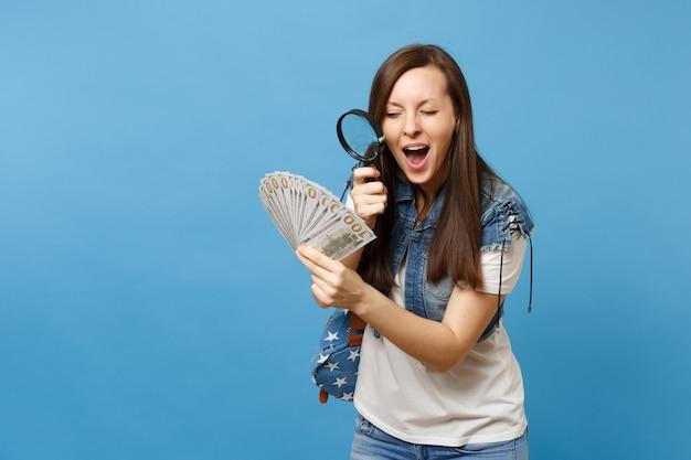 Młoda podejrzana studentka z plecakiem patrząc na pakiet wiele dolarów, gotówka z lupą sprawdzająca banknoty na białym tle na niebieskim tle. weryfikacja autentyczności pieniędzy.