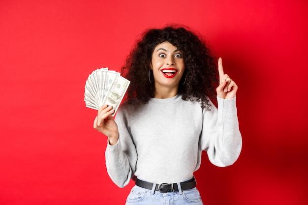 Młoda podekscytowana kobieta ma pomysł, jak zarabiać pieniądze, pokazując banknoty dolarowe i podnosząc palec w znaku eureka, stojąc na czerwonym tle