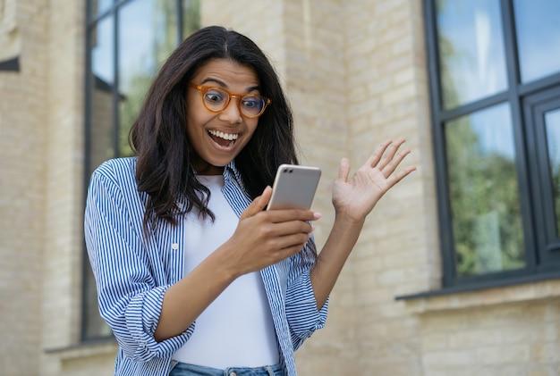 Młoda podekscytowana kobieta przy użyciu telefonu komórkowego zakupy online