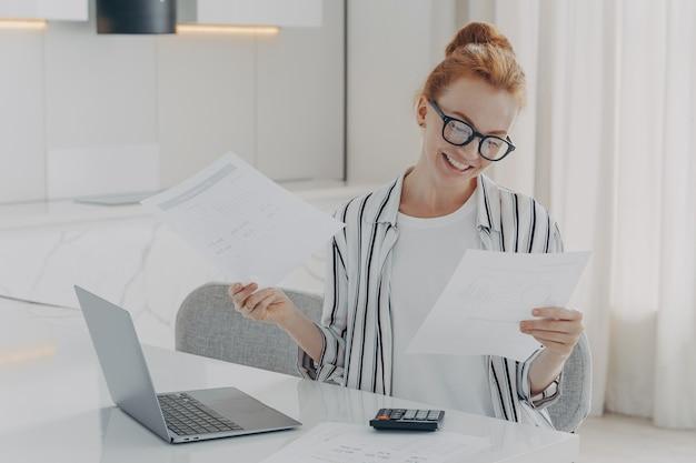 Młoda podekscytowana ruda kobieta siedzi przy stole w domu, czując się szczęśliwa po sprawdzeniu rachunków krajowych