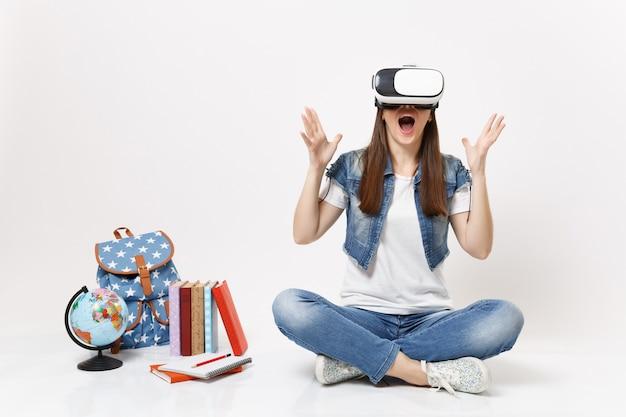 Młoda podekscytowana studentka nosząca okulary wirtualnej rzeczywistości rozkładająca ręce, ciesząca się siedzeniem w pobliżu kuli ziemskiej, plecaka, podręczników szkolnych na białym tle