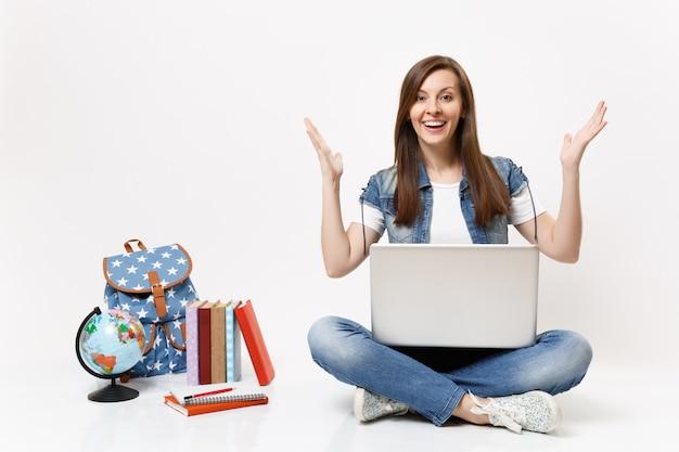 Młoda podekscytowana zdumiona studentka trzymająca laptopa i rozkładająca ręce siedząca w pobliżu kuli ziemskiej, plecaka, podręczników szkolnych