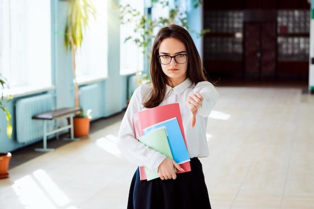 Młoda podrażniona studentka pokazuje kciuk w dół