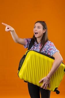 Młoda podróżna kobieta ubrana w czerwone okulary przeciwsłoneczne na głowie stojącej z plecakiem trzymając walizkę wskazując palcem w bok patrząc zaskoczony na pomarańczowym tle