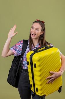 Młoda podróżna kobieta ubrana w czerwone okulary przeciwsłoneczne na głowie z plecakiem trzymającym walizkę, machająca ręką podczas powitania lub gestu pożegnania, uśmiechnięta ze szczęśliwą twarzą nad odizolowaną zielenią