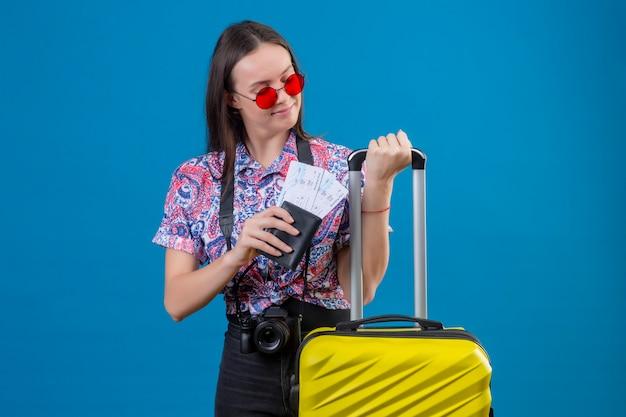 Młoda podróżna kobieta ubrana w czerwone okulary przeciwsłoneczne, stojąca z żółtą walizką, trzymając paszport i bilety, patrząc na bok pozytywnie i szczęśliwie na niebieskim tle
