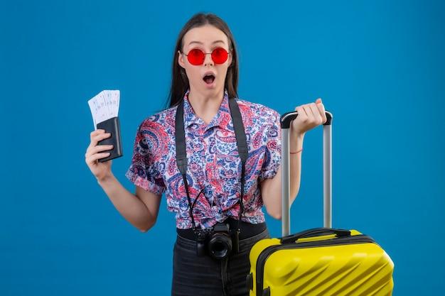 Młoda podróżna kobieta ubrana w czerwone okulary przeciwsłoneczne, stojąca z żółtą walizką, trzymająca paszport i bilety, patrząc zaskoczona i zdumiona na niebieskim tle