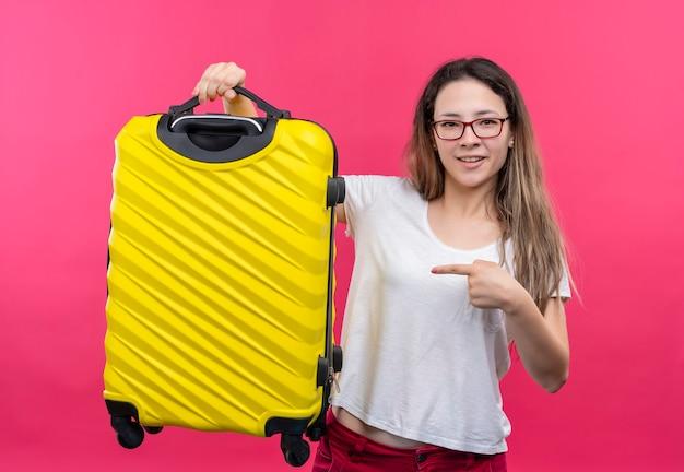 Młoda podróżna kobieta w białej koszulce trzyma walizkę podróżną, wskazując palcem wskazującym na to, uśmiechając się pewnie stojąc nad różową ścianą