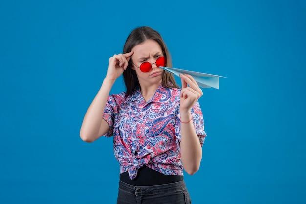 Młoda podróżna kobieta w czerwonych okularach przeciwsłonecznych, trzymając papierowy samolot, patrząc na niego z marszczoną miną niezadowolona, mając wątpliwości stojąc na niebieskim tle