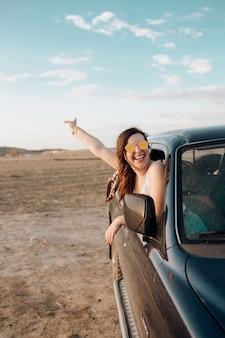 Młoda podróżnicza kobieta ma zabawę z gitarą w jeepowym samochodzie 4x4 robi wakacje podróżowi o zachodzie słońca