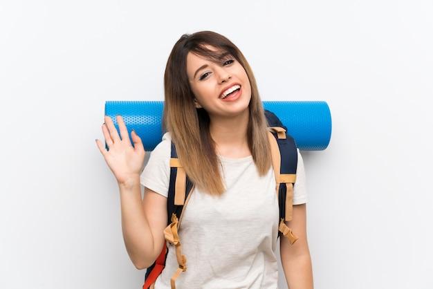 Młoda podróżnicza kobieta nad biel ścianą salutuje z ręką z szczęśliwym wyrażeniem