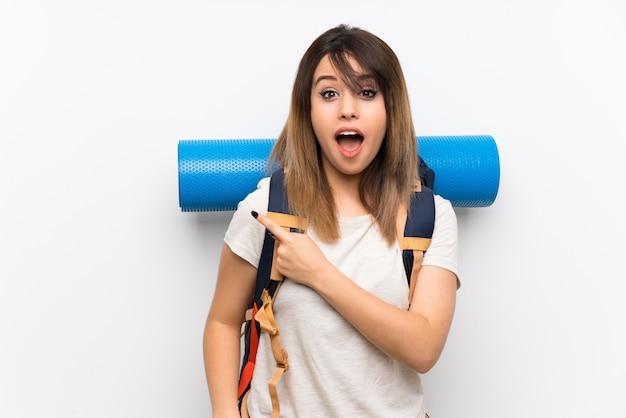 Młoda podróżnicza kobieta nad biel ścianą zaskakującą i wskazuje stronę