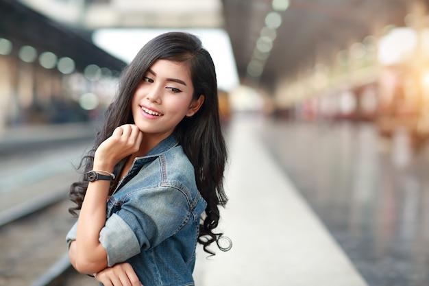 Młoda podróżnicza kobieta z kurtki cajgowym czekaniem dla pociągu