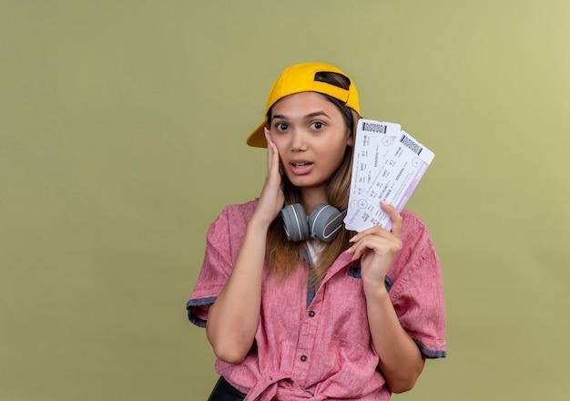 Młoda podróżniczka dziewczyna ubrana w różową koszulę w czapce ze słuchawkami na szyi, trzymająca bilety lotnicze, patrząc zdziwiona i zaskoczona ręką na twarzy