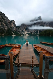 Młoda podróżniczka dziewczyna z kapeluszem i plecakiem vintage na molo w lago di braies otoczonym górami włoskich alp
