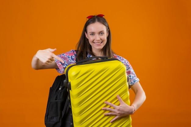 Młoda podróżniczka kobieta ubrana w czerwone okulary przeciwsłoneczne na głowie stojąca z plecakiem trzymająca walizkę patrząc na kamerę i wskazująca palcem na walizkę uśmiechnięta ze szczęśliwą twarzą na pomarańczowym tle