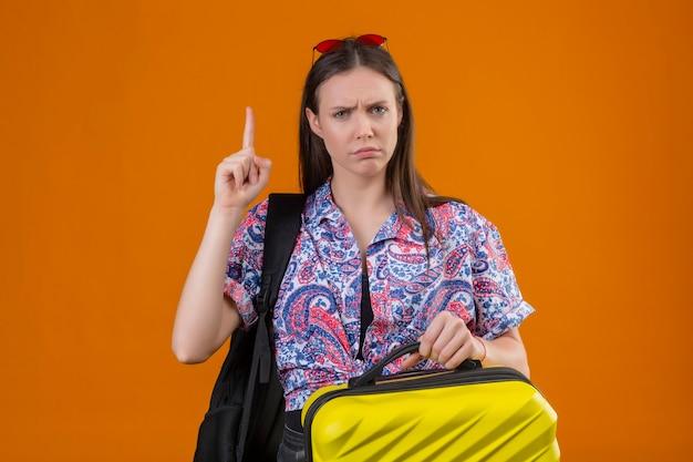 Młoda podróżniczka kobieta ubrana w czerwone okulary przeciwsłoneczne na głowie stojąca z plecakiem trzymająca walizkę patrząc na kamerę marszcząc brwi stojąc z palcem w górę ostrzeżenie o niebezpieczeństwie na pomarańczowym tle