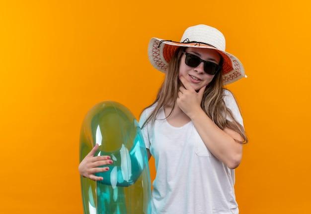 Młoda podróżniczka kobieta w białej koszulce na sobie letni kapelusz trzyma nadmuchiwany pierścień patrząc z zamyśleniem na twarzy stojącej nad pomarańczową ścianą