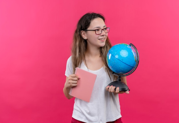 Młoda podróżniczka kobieta w białej koszulce trzyma kulę ziemską i notatnik patrząc na bok uśmiechnięty pozytywny i szczęśliwy stojący nad różową ścianą