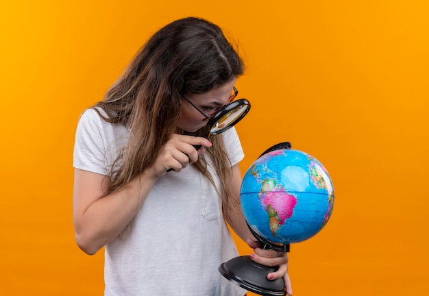 Młoda podróżniczka kobieta w białej koszulce trzyma kulę ziemską patrząc na nią przez szkło powiększające, patrząc zaskoczony stojąc nad pomarańczową ścianą
