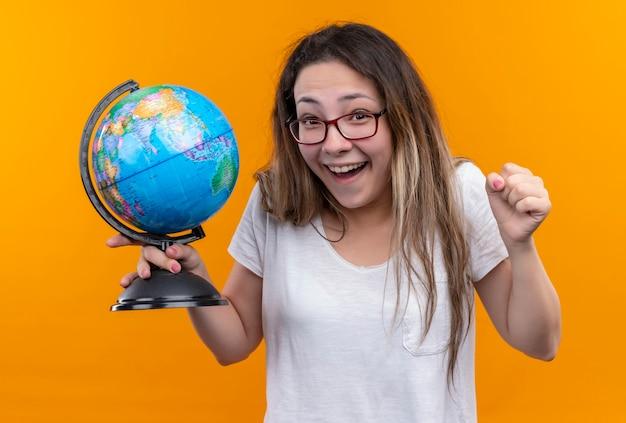 Młoda podróżniczka kobieta w białej koszulce trzyma kulę ziemską patrząc podekscytowany i szczęśliwy, zaciskając pięść stojącą na pomarańczowej ścianie