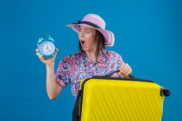 Młoda podróżniczka kobieta w letnim kapeluszu stojąca z żółtą walizką trzymająca budzik patrząc na niego zszokowana wstydem za błąd wyrażenie strachu na niebieskim tle