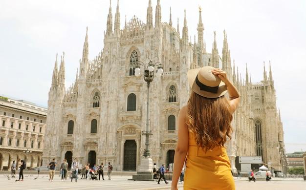 Młoda podróżniczka odwiedzająca katedrę w mediolanie we włoszech. moda kobieta turysta stojący na placu piazza duomo w mediolanie.