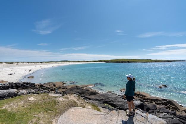 Młoda podróżniczka podziwiająca wspaniałe krajobrazy na plaży dogs bay w galway w irlandii