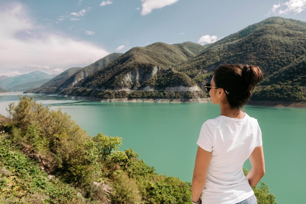 Młoda podróżniczka siedzi i patrzy na piękny widok na zalew zhinvalskoe w gruzji.
