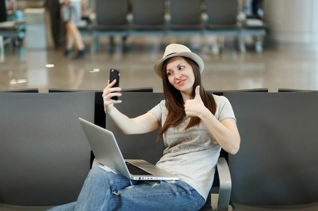 Młoda podróżniczka turystyczna kobieta pracuje na laptopie, robi selfie na telefonie komórkowym, pokazuje kciuk w górę, czeka w holu na lotnisku