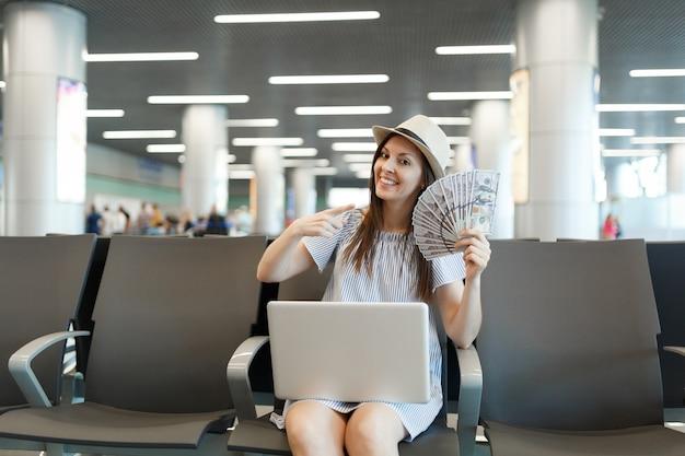 Młoda podróżniczka turystyczna kobieta pracuje na laptopie wskazując palcem wskazującym na pakiet dolarów, gotówkę, czekaj w holu na lotnisku