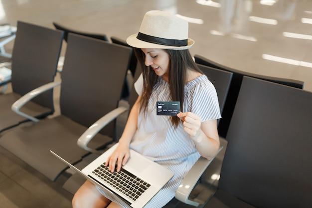 Młoda podróżniczka turystyczna kobieta w kapeluszu pracuje na laptopie i trzyma kartę kredytową podczas oczekiwania w holu na międzynarodowym lotnisku