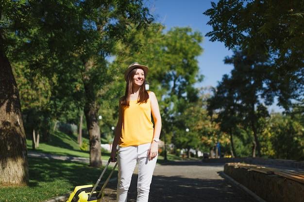 Młoda podróżniczka turystyczna kobieta w żółtych letnich ubraniach, kapelusz z walizką, patrząc na bok, spacerując po mieście na świeżym powietrzu. dziewczyna wyjeżdża za granicę na weekendowy wypad. styl życia podróży turystycznej.