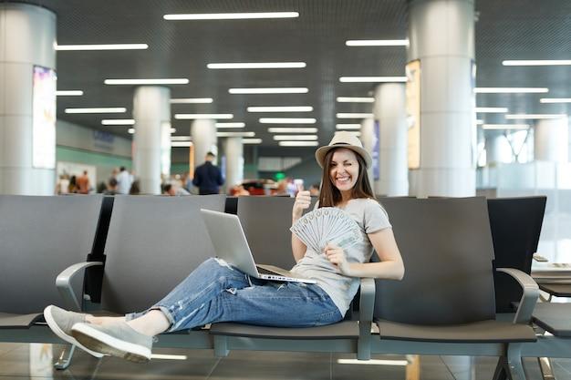 Młoda podróżniczka turystyczna kobieta z laptopem, trzyma pakiet dolarów, gotówka pokazując kciuk do góry migający, czekaj w holu na lotnisku