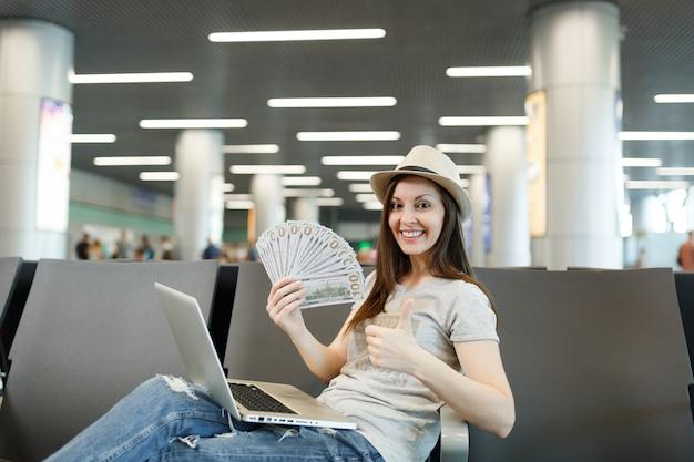 Młoda podróżniczka turystyczna kobieta z laptopem trzymająca pakiet dolarów, gotówka, pokazująca kciuk do góry, czekająca w holu na lotnisku