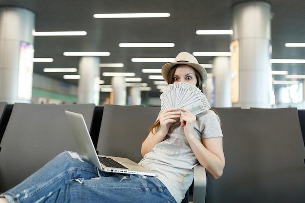 Młoda podróżniczka turystyczna kobieta z laptopem zakrywającym twarz z pakietem dolarów, gotówką podczas oczekiwania w holu na lotnisku