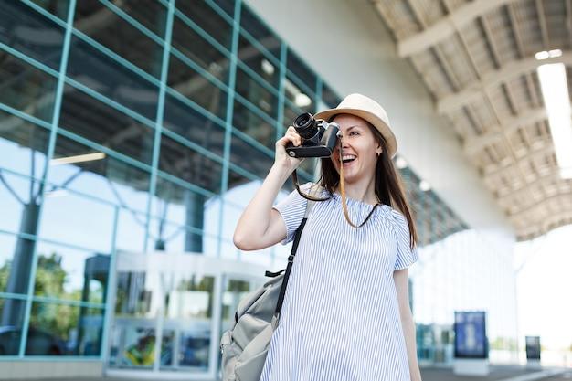 Młoda podróżniczka turystyczna kobieta z plecakiem robi zdjęcia na retro vintage aparat fotograficzny na międzynarodowym lotnisku