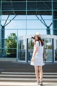 Młoda podróżniczka turystyczna kobieta z plecakiem robi zdjęcia retro aparatem fotograficznym na przejściu dla pieszych na międzynarodowym lotnisku