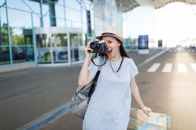 Młoda podróżniczka turystyczna kobieta z plecakiem trzymająca retro vintage aparat fotograficzny, papierową mapę na międzynarodowym lotnisku