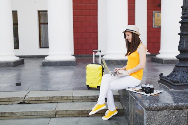 Młoda podróżniczka turystyczna kobieta z walizką siedzącą na schodach przy użyciu pracy na komputerze typu laptop w mieście na świeżym powietrzu. dziewczyna wyjeżdża za granicę na weekendowy wypad. koncepcja życia podróż turystyka.