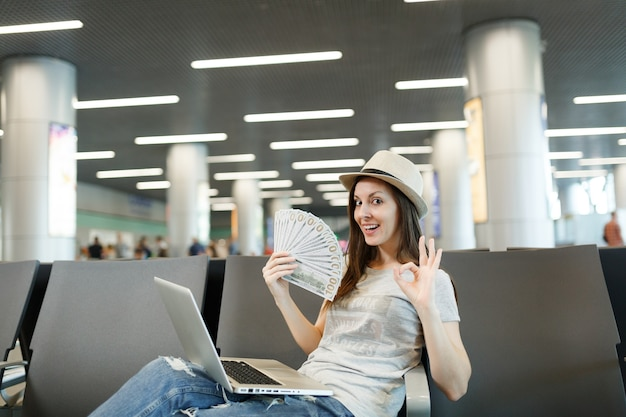 Młoda podróżniczka turystyczna z laptopem trzymająca pakiet dolarów, gotówka, pokazująca znak ok, czekająca w holu na lotnisku