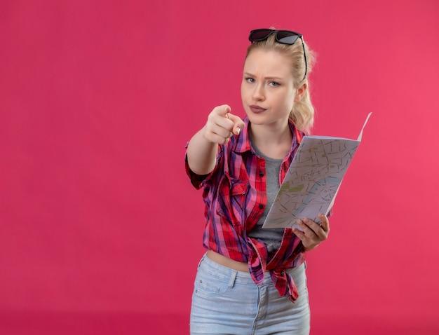 Młoda podróżniczka ubrana w czerwoną koszulę i okulary na głowie trzymając mapę pokazuje gest na na białym tle różowej ścianie