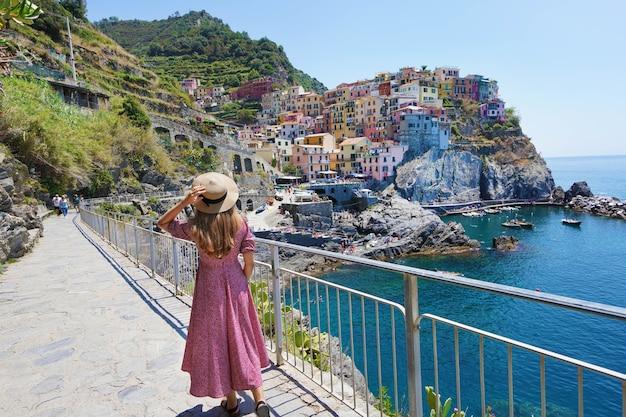 Młoda podróżniczka w kapeluszu i sukience schodzi wzdłuż promenady manaroli, patrząc na fantastyczny panoramiczny widok na wioskę manarola w cinque terre, włochy