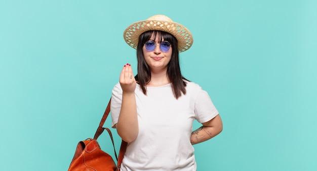 Młoda podróżniczka wykonująca gest kaprysu lub pieniędzy, mówiąca o spłacie długów!