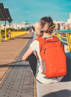 Młoda podróżniczka z plecakiem siedzi na molo i patrzy na morze