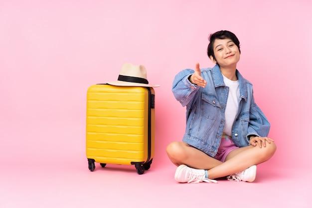 Młoda podróżniczka z walizką siedzącą na podłodze nad różowymi drżącymi rękami za zamknięcie dobrej oferty
