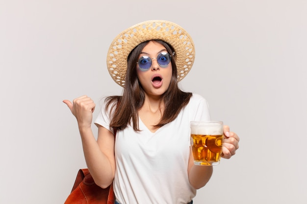 Młoda podróżniczka zdziwiona wyrazem twarzy i trzyma piwo