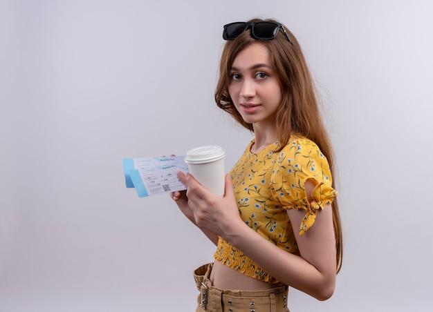 Młoda podróżnik dziewczyna nosi okulary przeciwsłoneczne na głowie trzymając bilety lotnicze i plastikową filiżankę kawy na odosobnionej białej ścianie z miejsca na kopię